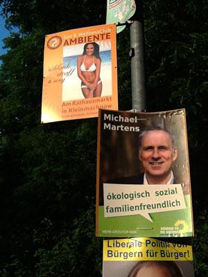 Wahlplakate und Werbung an einem Laternenpfahl