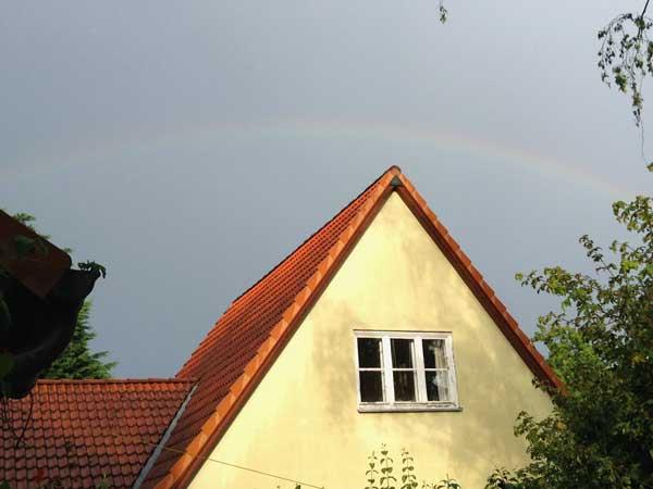Regenbogen über Hausdach
